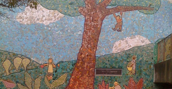 Portion of Grattan School mural depicting children playing on and around a large tree
